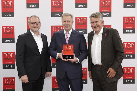 Christian Wulff überreicht Seminarleiter und Berater Michael Flegel (links) und Geschäftsführer Cay von Fournier (rechts) die Auszeichnung als Top Consultant 2017.
